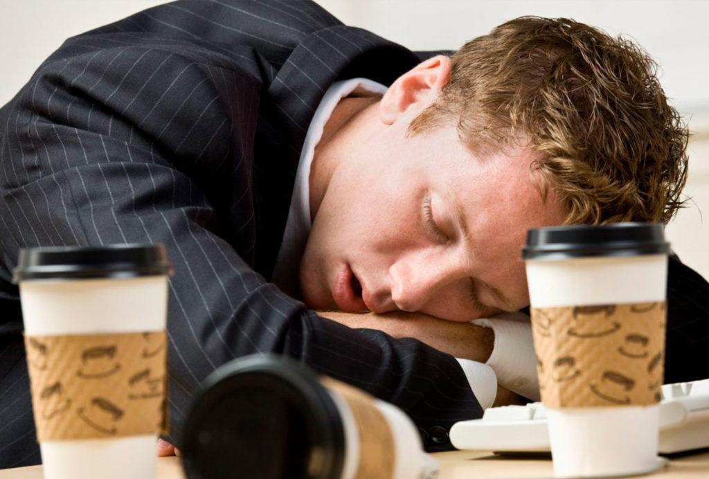 Mand der sover på arbejdet omringet af kaffekopper